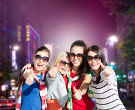 Group of young women showing thumbs up in city. Holidays, friendsip, nightlife and happy people concept - happy teenage girls or young women showing thumbs up Stock Photography