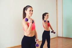 Group of young women in sportswear with dumbbells exercising at the gym. Royalty Free Stock Images