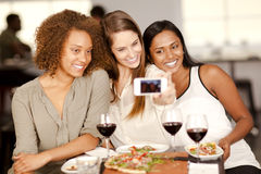 Group of young women taking a selfie photo. With a smartphone in a restaurant Royalty Free Stock Photography