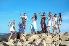 Group of young womens standing together at a beach on a summer day. Happy young people enjoying a day at beach. royalty free stock photo