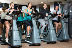 Group  young  working out of cycling in fitness club. Group young happy working out of cycling in modern fitness club Royalty Free Stock Photography