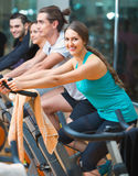 Group young  working out of cycling in fitness club. Group young working out of cycling in modern fitness club Royalty Free Stock Images