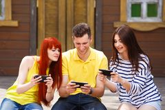 Group of youth laughing playing mobile video game outdoors. Three young friends have fun for entertainment.Gamer excitement, face expression royalty free stock photo