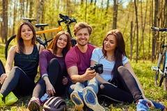 Groupe людей ослабляя после велосипеда едет в лесе Стоковая Фотография
