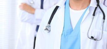 Groupe неизвестных докторов стоя прямо в офисе больницы Закройте вверх стетоскопа на груди практикующий врача стоковое фото rf