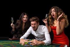 Groupe adulte célébrant l'ami gagnant à la roulette Photographie stock libre de droits