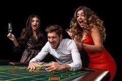Groupe adulte célébrant l'ami gagnant à la roulette Photo libre de droits