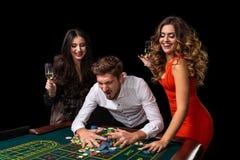 Groupe adulte célébrant l'ami gagnant à la roulette Photos libres de droits