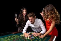Groupe adulte célébrant l'ami gagnant à la roulette Photos stock