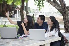 Groupe asiatique d'étudiants à l'aide du comprimé et du carnet partageant avec t Image libre de droits