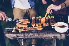 Groupe asiatique d'amis ayant le barbecue extérieur de jardin riant W Photographie stock