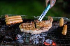 Groupe asiatique d'amis ayant le barbecue extérieur de jardin riant W Image libre de droits