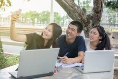 Groupe asiatique de sourire et de selfie d'étudiants avec l'ami photographie stock