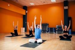 Groupe avec l'entraîneur s'asseyant dans la pose de yoga Images libres de droits