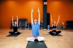 Groupe avec l'entraîneur s'asseyant dans la pose de yoga Photos libres de droits
