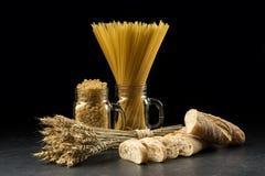 Groupe, baguette, macaronis et pâtes de blé dans le pot, sur le fond noir Bouquet et pain de grain sur la table en bois foncée or Photos stock