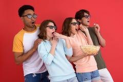 Groupe choqué d'amis observant le film mangeant du maïs éclaté Photographie stock libre de droits