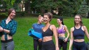 Groupe cinq actifs d'aller femelle de sourire pour la séance d'entraînement, tenant des tapis de yoga dans le matin d'été au parc clips vidéos