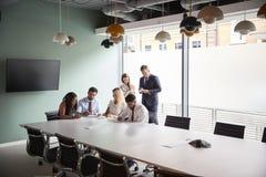Groupe collaborant sur la tâche au jour licencié d'évaluation de recrutement tandis qu'étant observé par l'équipe de recrutement photo libre de droits