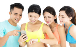 Groupe convenable de jeunes heureux observant le téléphone et la montre intelligents Photo stock