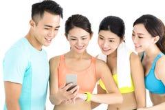 Groupe convenable de jeunes heureux observant le téléphone et la montre intelligents Photos libres de droits