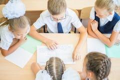 Groupe d'écoliers à la salle de classe d'école se reposant au bureau Images stock
