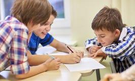 Groupe d'écoliers écrivant ou dessinant à l'école Image stock