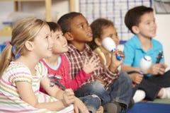 Groupe d'écoliers élémentaires d'âge dans la classe de musique avec des instruments Image stock