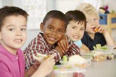 Groupe d'écoliers élémentaires d'âge mangeant le déjeuner emballé sain dans la classe images libres de droits