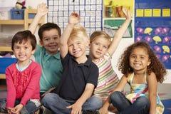 Groupe d'écoliers élémentaires d'âge répondant à la question dans la classe Images stock