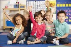 Groupe d'écoliers élémentaires d'âge répondant à la question dans la classe Image libre de droits