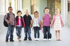 Groupe d'écoliers élémentaires d'âge se tenant dehors Image stock