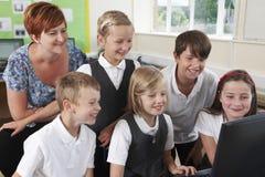 Groupe d'élèves élémentaires dans la classe d'ordinateur avec le professeur images stock
