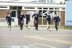 Groupe d'élèves d'école primaire fonctionnant dans le terrain de jeu Photos stock