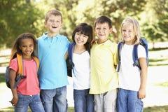 Groupe d'élèves d'école primaire utilisant des sacs à dos en parc Images stock