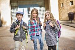 Groupe d'élèves primaires en dehors de salle de classe Image stock