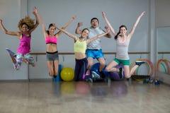 Groupe d'équipe de forme physique sautant dans le studio de forme physique Images stock