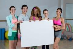 Groupe d'équipe de forme physique tenant la plaquette vide Image libre de droits