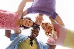 Groupe d'étreindre heureux d'amis Image stock