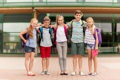 Groupe d'étreindre heureux d'étudiants d'école primaire Photo stock