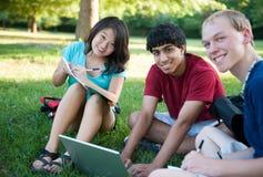 Groupe d'étude heureuse de trois adolescents Photographie stock libre de droits