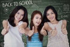 Groupe d'étudiantes avec des pouces  Photo stock