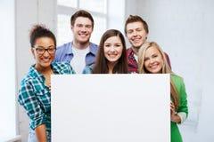 Groupe d'étudiants à l'école avec le conseil vide Photo stock