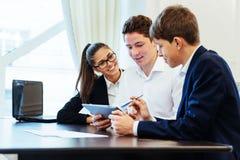 Groupe d'étudiants étudiant utilisant un ordinateur portable Images stock