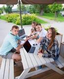 Groupe d'étudiants adolescents au parc avec l'ordinateur Photographie stock libre de droits