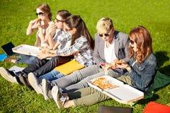 Groupe d'étudiants adolescents mangeant de la pizza sur l'herbe Image stock
