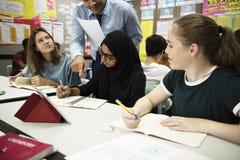 Groupe d'étudiants apprenant dans la salle de classe Image stock