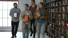 Groupe d'étudiants avec des livres marchant dans la bibliothèque clips vidéos