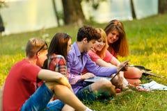 groupe d'étudiants avec l'ordinateur portable détendant en parc Photo libre de droits