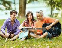 Groupe d'étudiants avec la guitare se reposant en parc sur ensoleillé Photo libre de droits